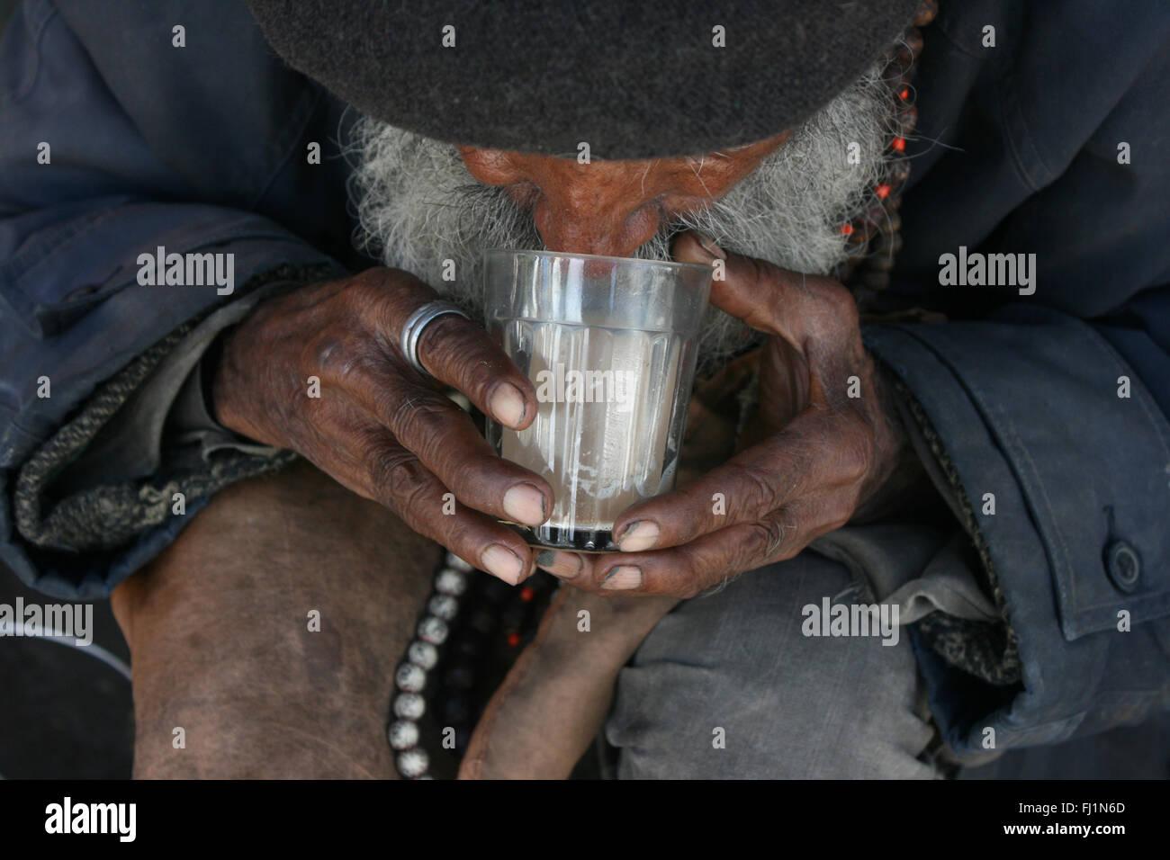 El pobre viejo hombre bebiendo té (chaï) en copa tradicional, Shimla, India Imagen De Stock