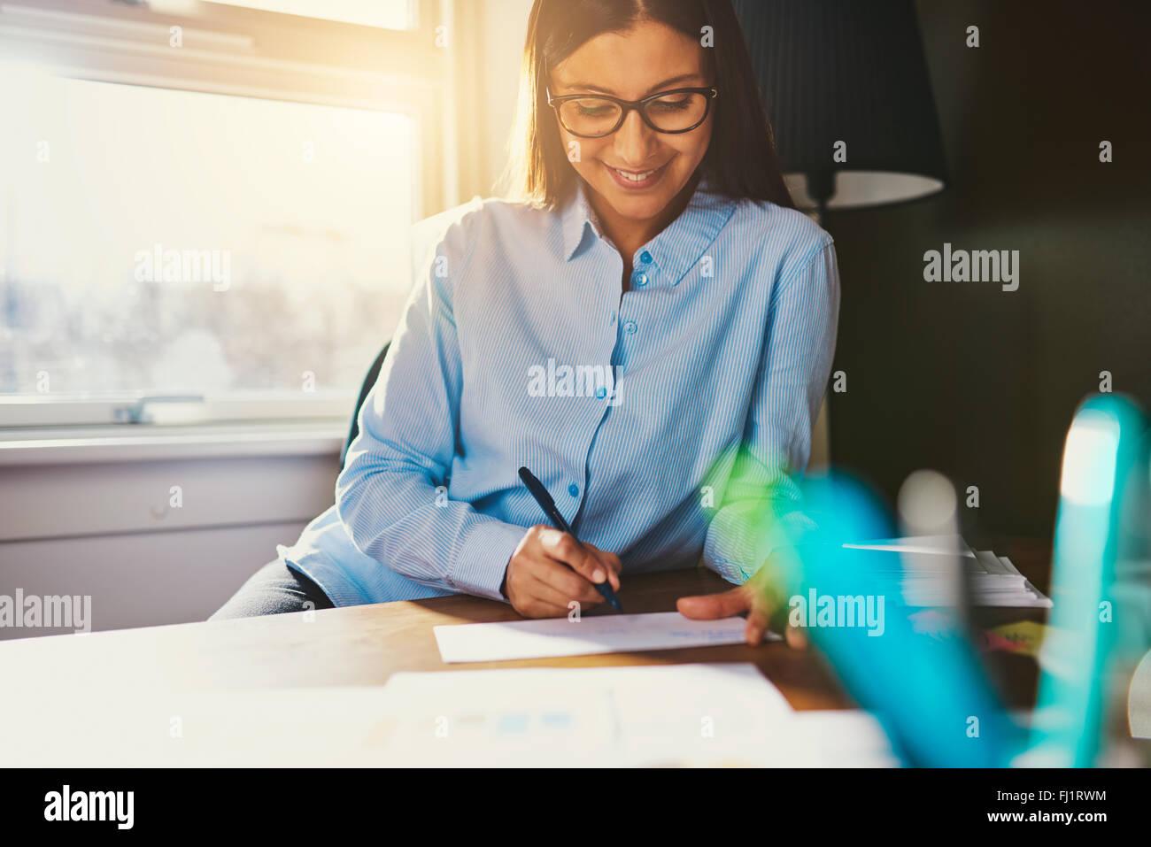 Mujer de negocios trabajando en un escritorio escribiendo una dirección en un sobre Imagen De Stock