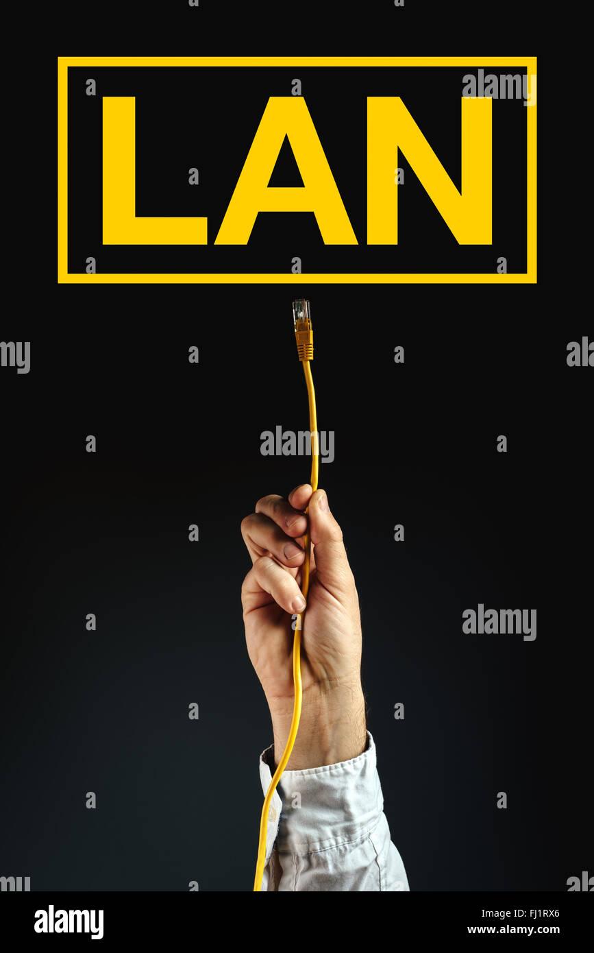 Empresario enchufando el cable LAN para conectarse a la red de área local, la solución empresarial. Imagen De Stock