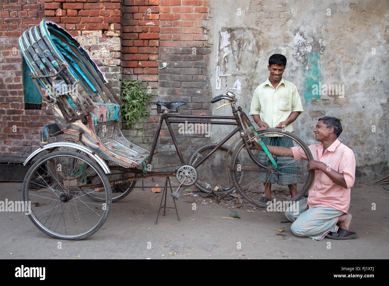 Un hombre sonriente reparaciones / cambia un rickshaw neumático desinflado con clientes satisfechos, Chittagong, Imagen De Stock