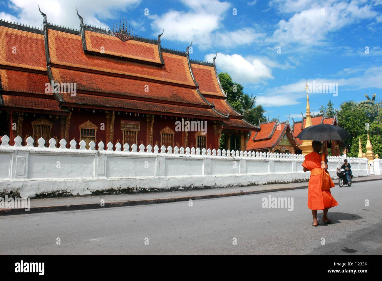 Monje budista caminando por las calles de Luang Prabang en frente del templo Wat Mai , Laos, Asia Imagen De Stock