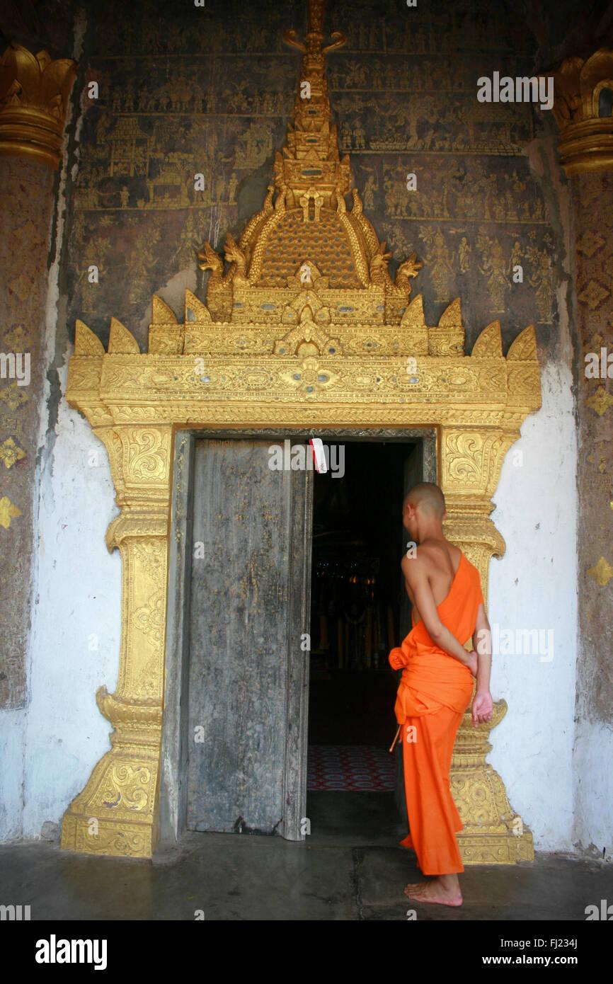 Monje budista en frente de una puerta en la entrada del templo en Luang Prabang, Laos, Asia Foto de stock