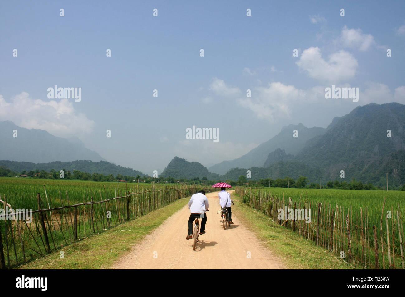 Dos personas de ciclismo en el típico paisaje alrededor de Vang Vieng village , Laos , el Sudeste de Asia Imagen De Stock