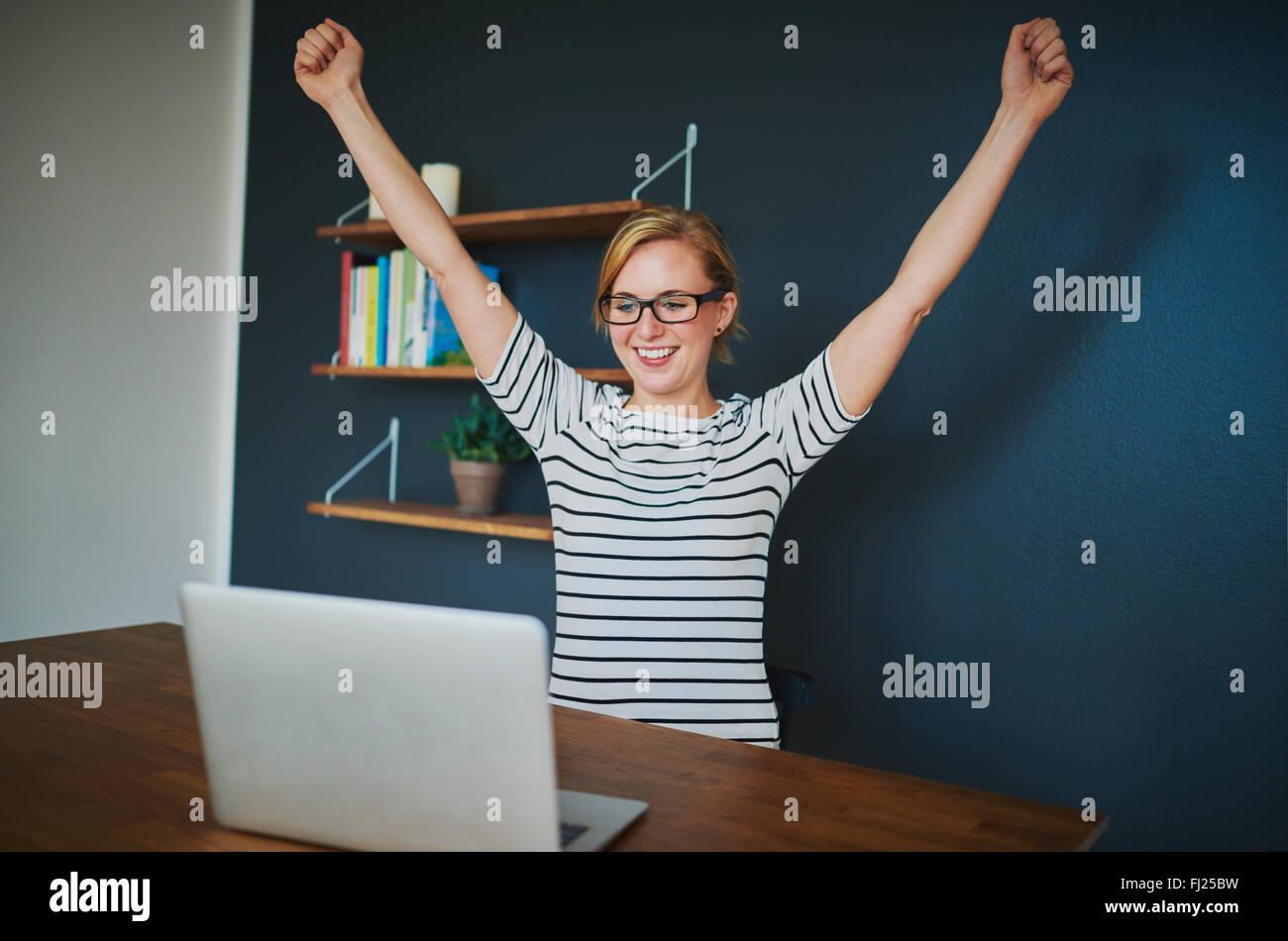 Emprendedor femenino en su oficina doméstica con los brazos levantados en éxito sentada con un portátil Imagen De Stock