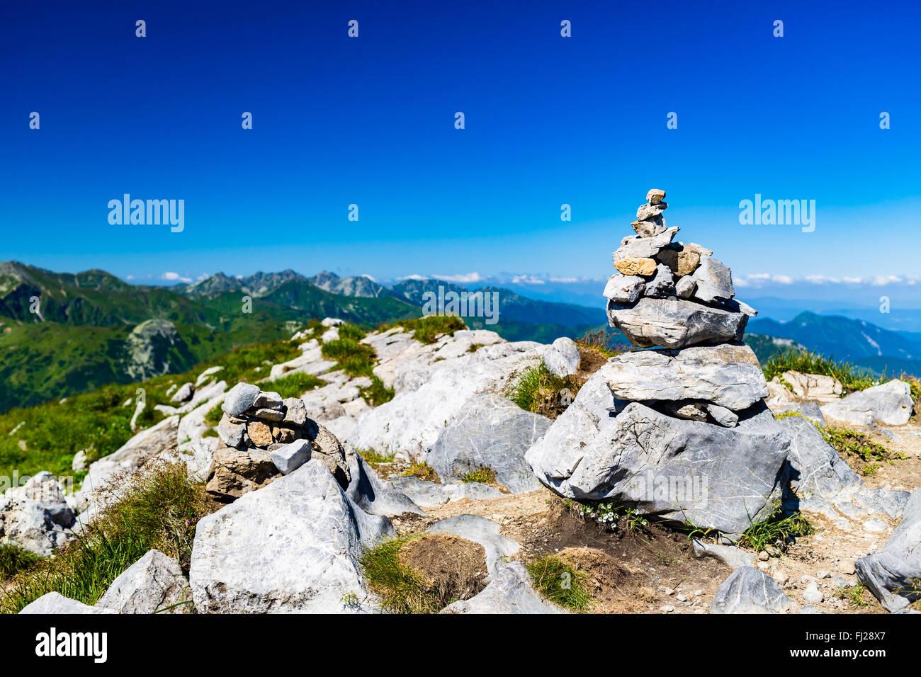 Paisaje de las montañas inspirador ver con piedras equilibrio signo de senderismo, día soleado en verano Imagen De Stock