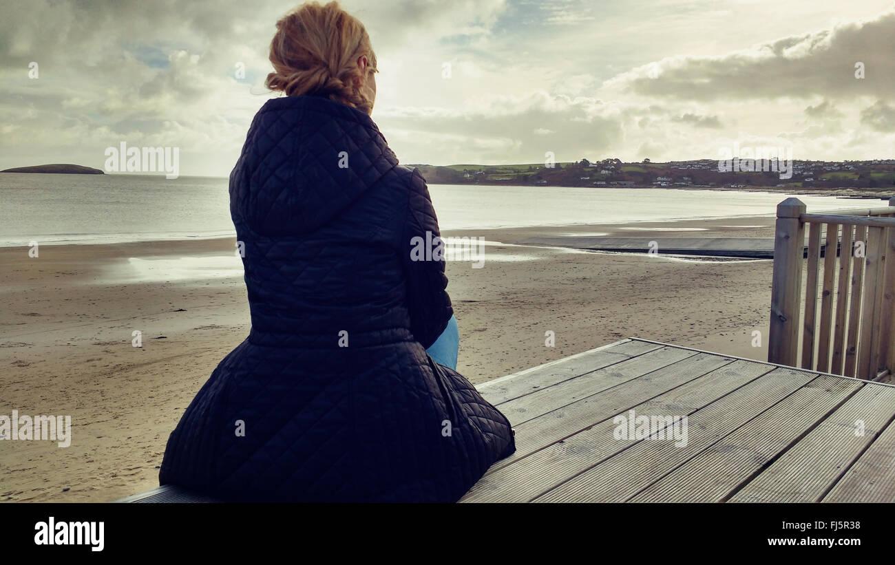 Elegante joven mujer sentada sobre madera en la playa Foto de stock