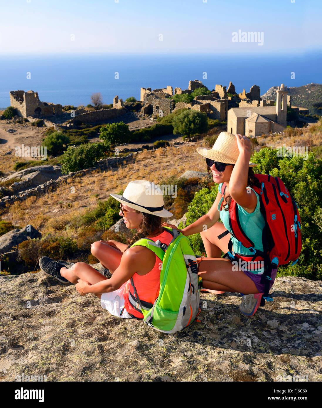 Dos mujeres excursionistas tomando un descanso, en el fondo el pueblo abandonado ruinas de Occi, Francia, Córcega Imagen De Stock