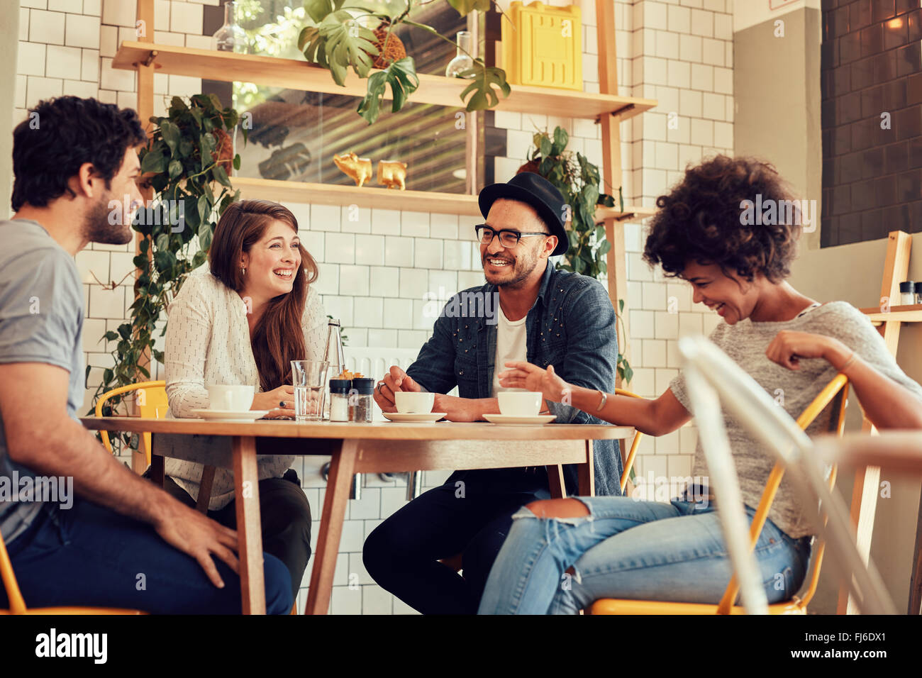 Grupo de amigos disfrutando en el café juntos. Los jóvenes reunidos en un café. Hombres y mujeres jóvenes sentados en la mesita de café y smilin Foto de stock