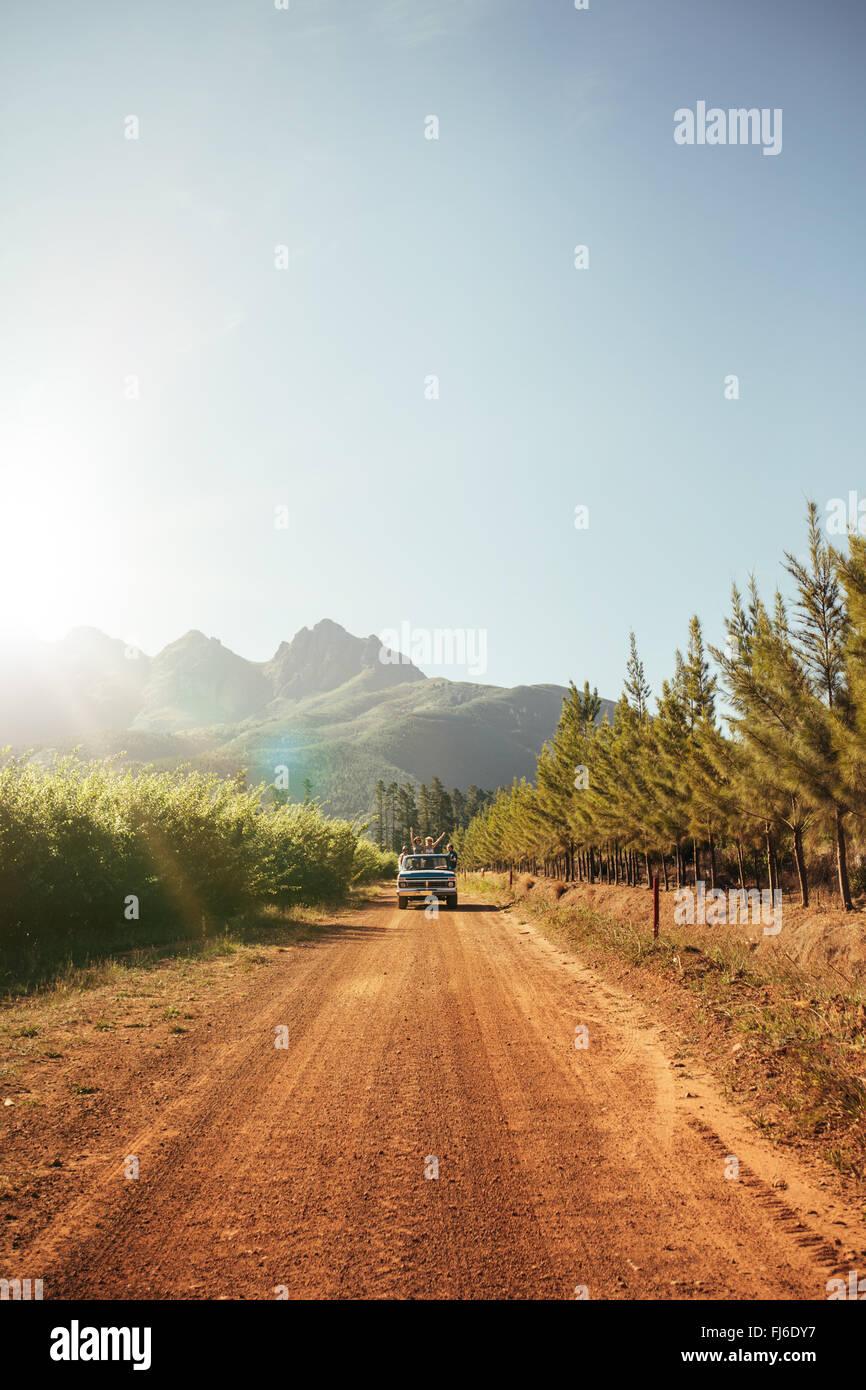 La imagen exterior del coche distante llegando en un camino de tierra rural en un día soleado. Conducción Imagen De Stock