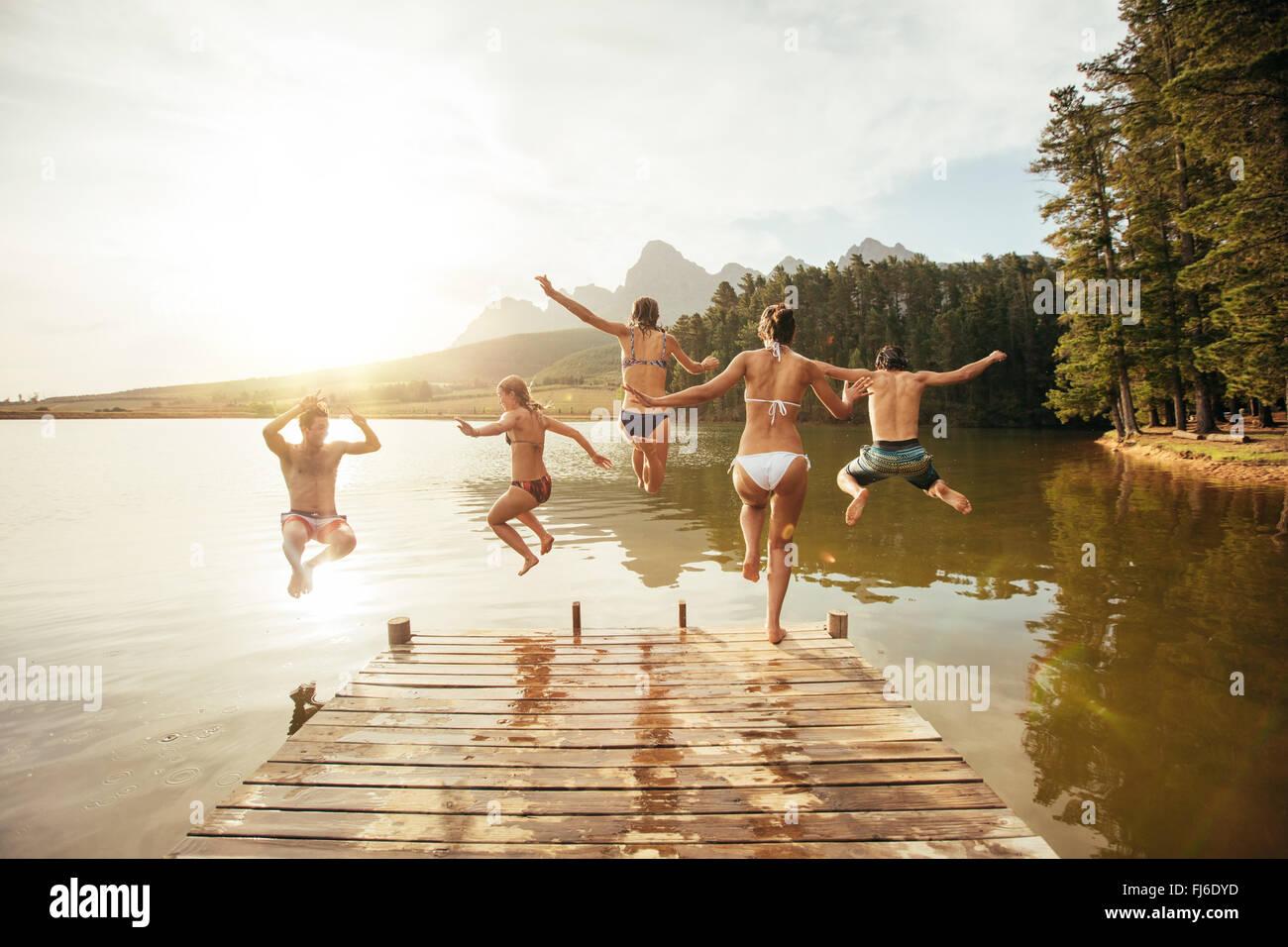 Retrato de jóvenes amigos saltar al agua desde una escollera. Los jóvenes se diviertan en el lago en un Imagen De Stock