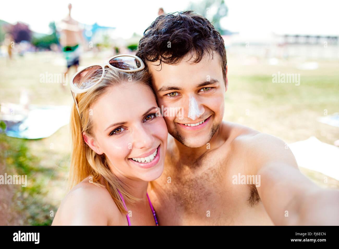 Pareja joven tomando el sol, tomando selfie. Protección solar en la nariz. Imagen De Stock