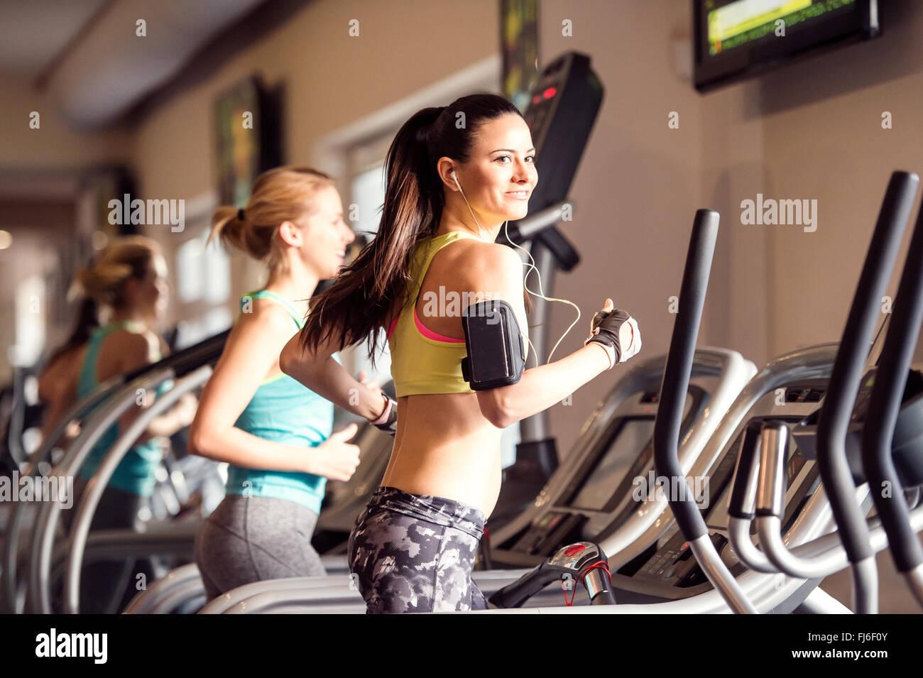 Colocar dos mujeres corriendo en cintas de correr en el gimnasio moderno Imagen De Stock