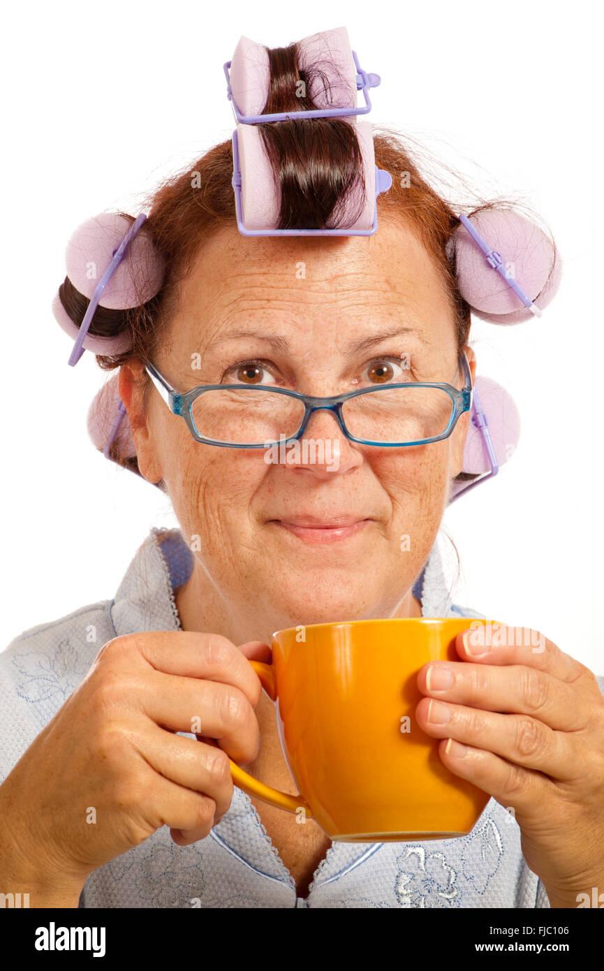 Alegre mujer de mediana edad con rizadores de pelo y taza de café Imagen De Stock