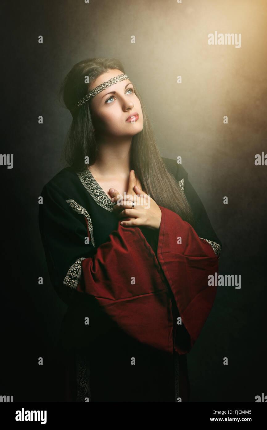 La bella ciudad medieval de mujer rezando en suave luz sagrada . Histórica y religión Foto de stock