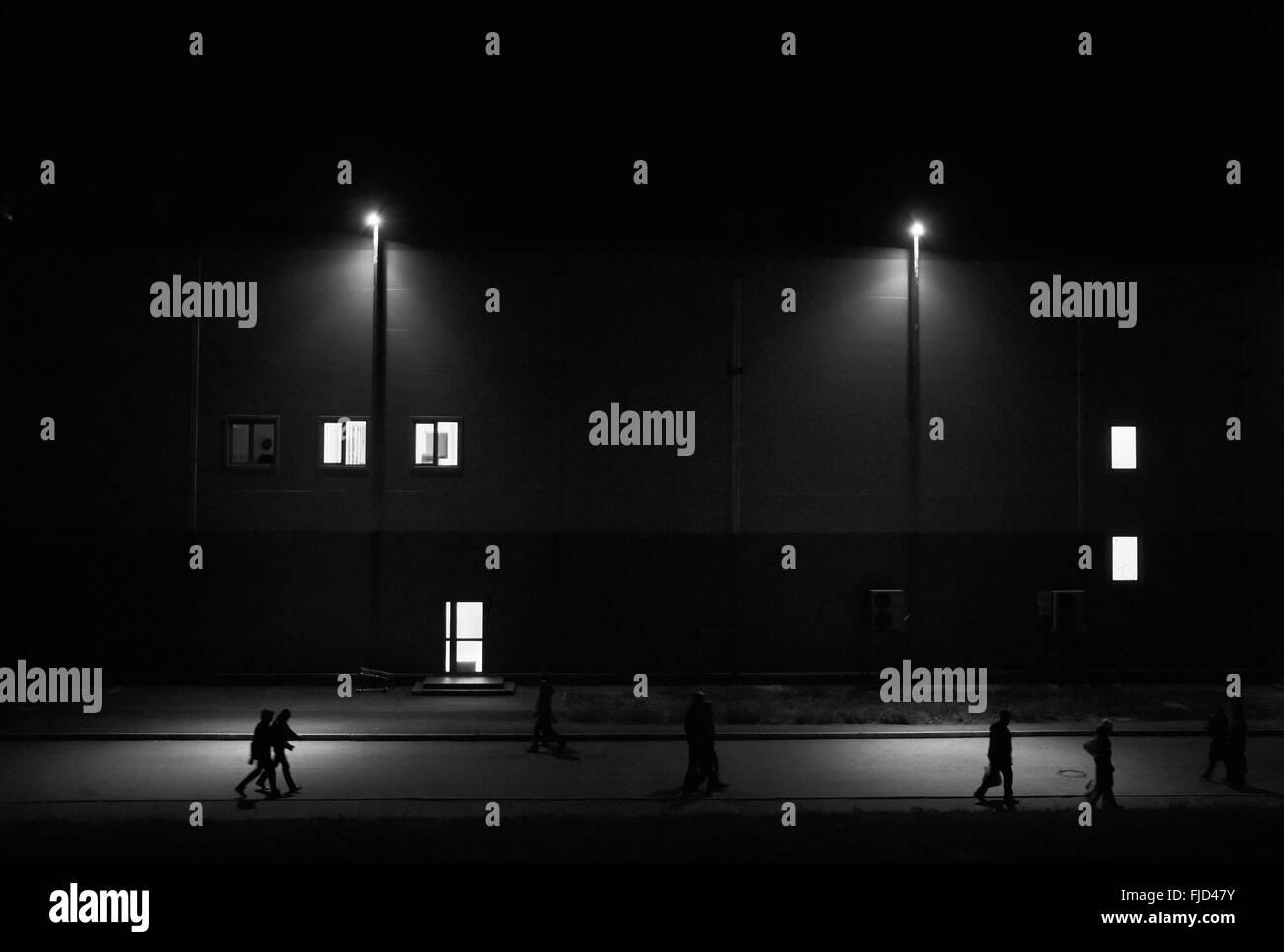 La gente caminando en la calle la noche con faroles contra el edificio con ventanas luminosas Imagen De Stock