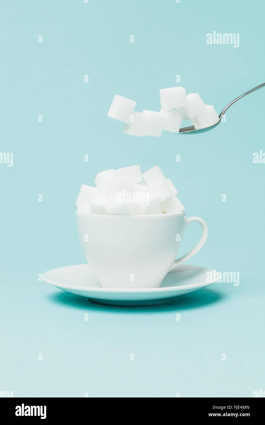 La adición de una cantidad excesiva de azúcar en una taza de té. Imagen De Stock