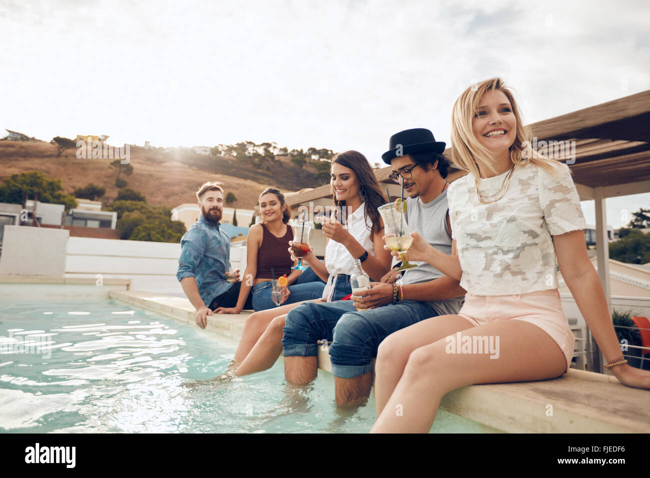 Grupo multiétnico de jóvenes paseándose por la piscina la celebración de cócteles. Feliz amigos disfrutando de fiesta en la piscina. Foto de stock