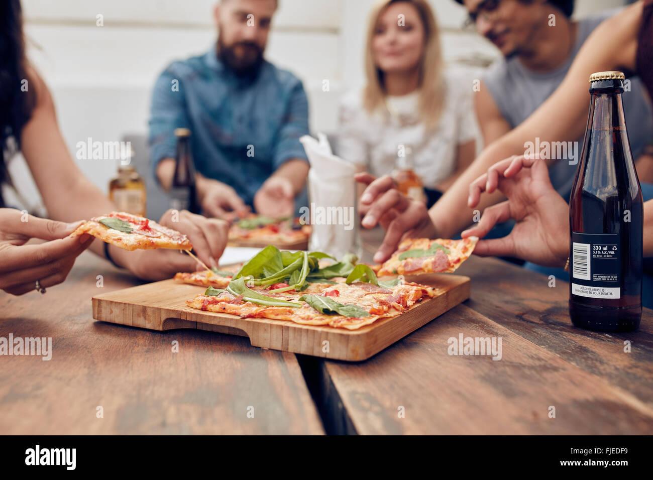 Primer plano de la pizza en la mesa, con un grupo de jóvenes sentados alrededor y recoger una porción. Imagen De Stock