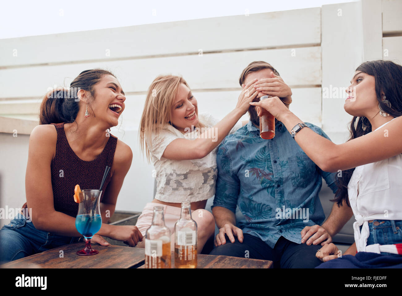 Foto de jóvenes amigos sentados juntos disfrutando de partido. Mujer cerrando los ojos de un hombre con otro Imagen De Stock