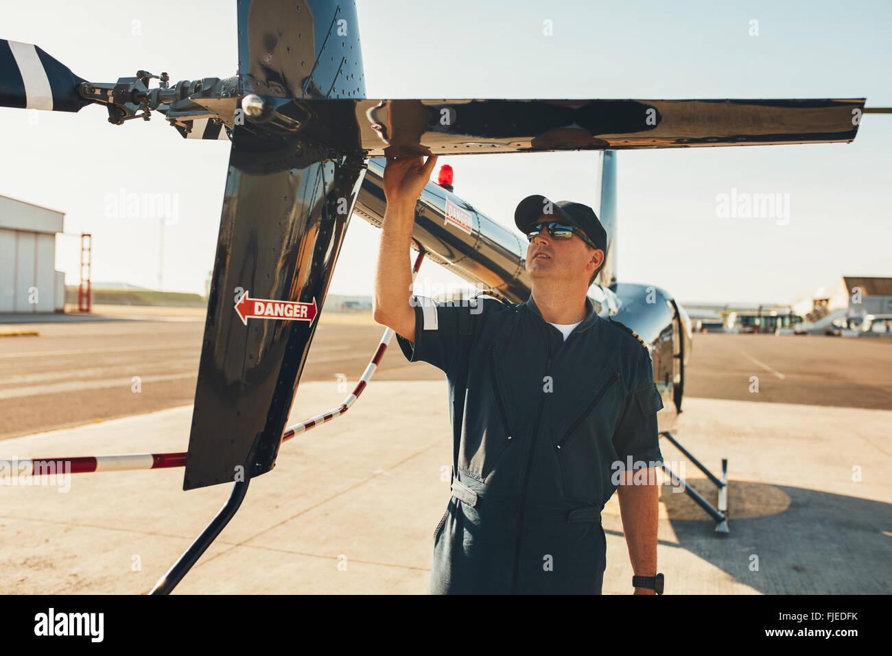 Hombres en uniforme de piloto de helicóptero de aleta trasera examinar. Inspección de pre vuelo por piloto en el aeropuerto. Foto de stock