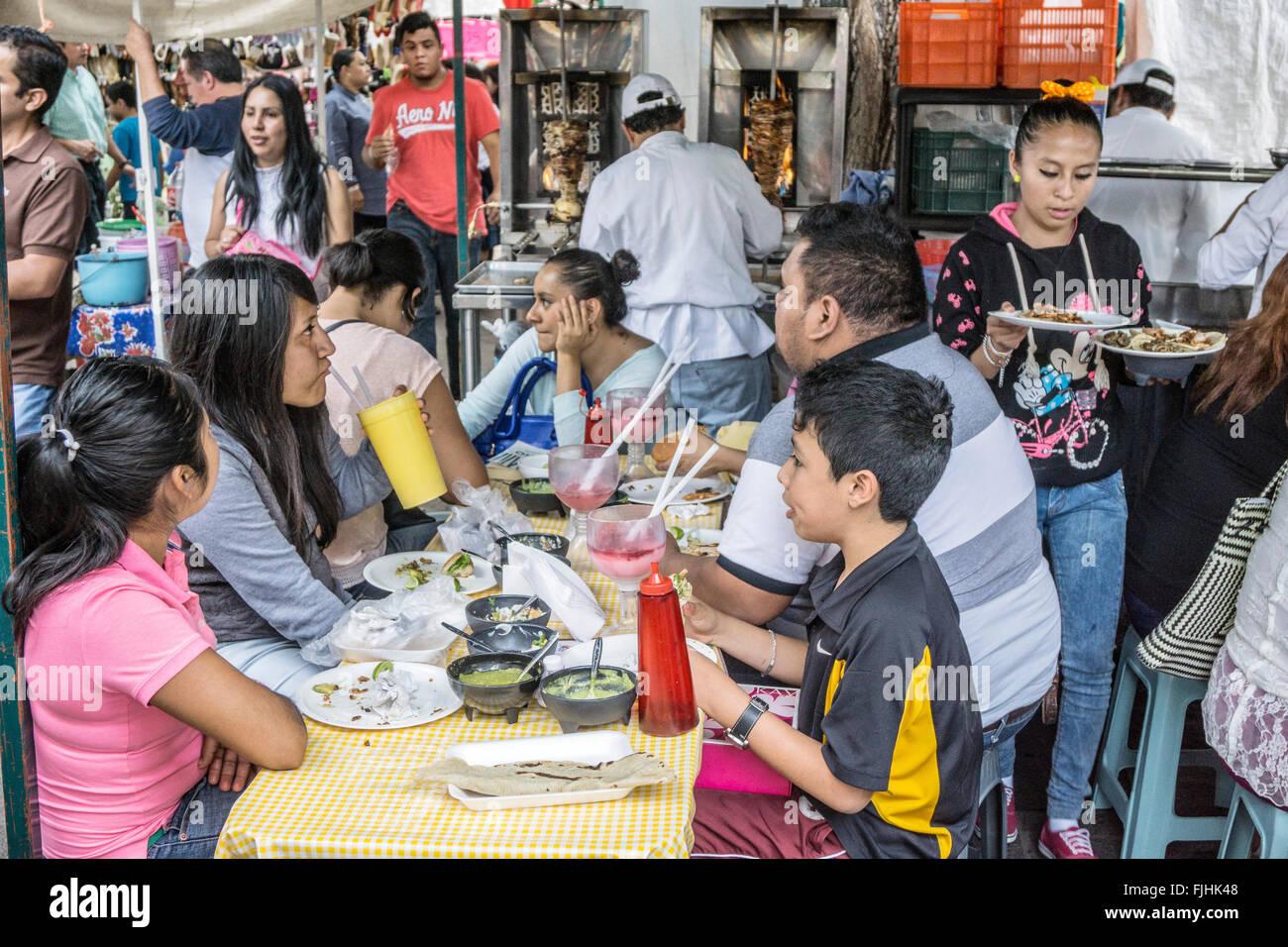 La familia se sienta a la mesa en sentarse puesto de comida en el mercado de los viernes parque Llano con cook en Imagen De Stock