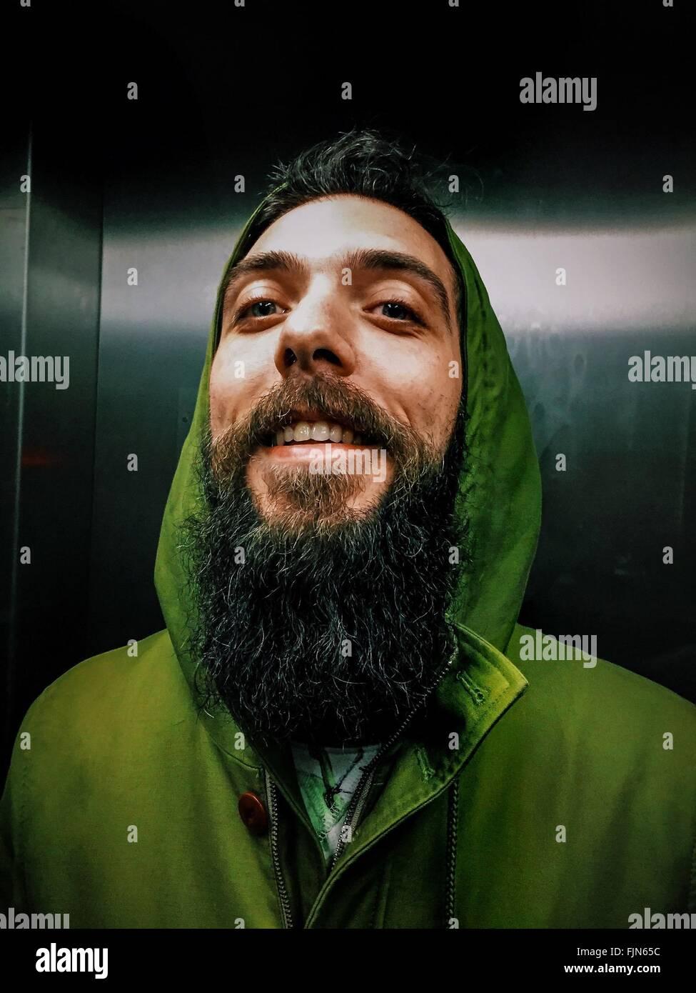 Alegre hombre joven con barba larga en el elevador Imagen De Stock