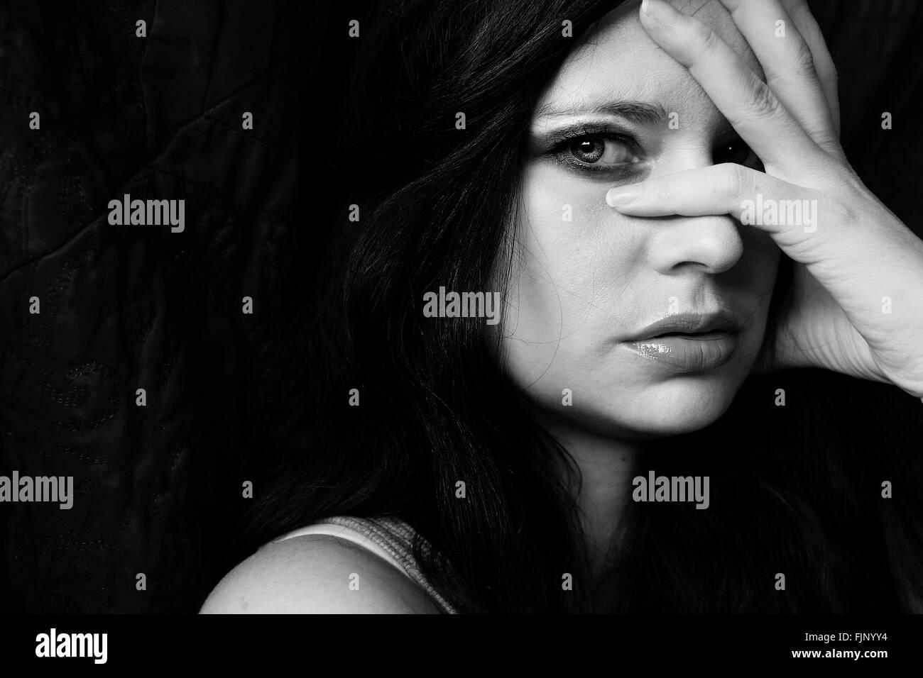 En primer plano reflexivo retrato de mujer joven con la mano en la cara contra el fondo negro Foto de stock
