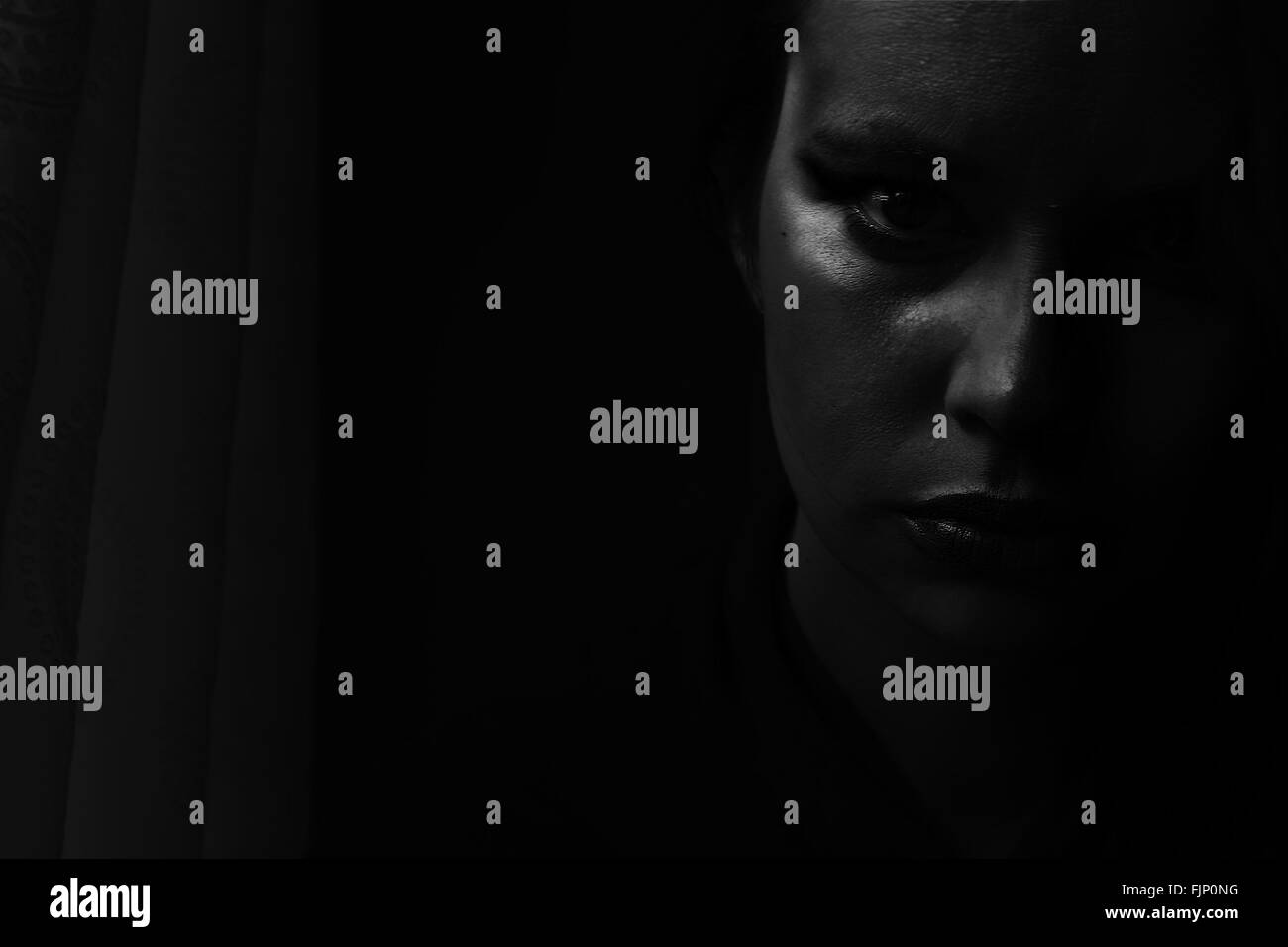 Retrato de mujer joven en el cuarto oscuro Imagen De Stock