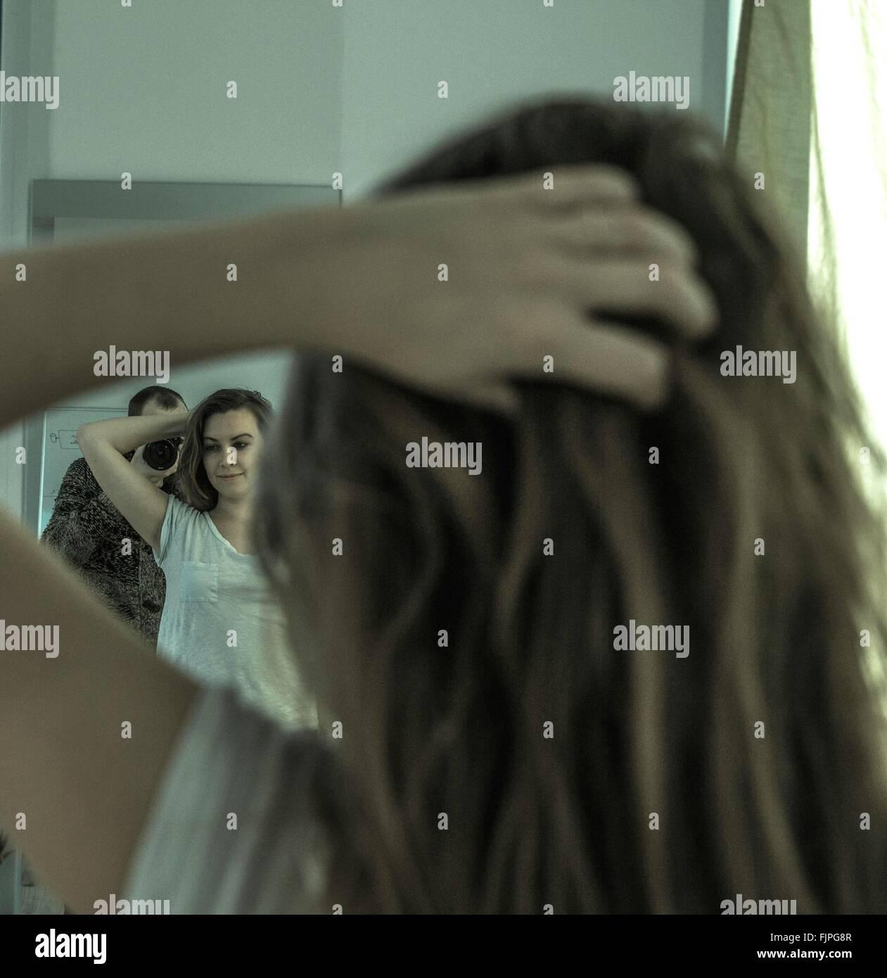 Hombre Mujer fotografía con la mano en el cabello mientras se refleja en el espejo en casa Imagen De Stock