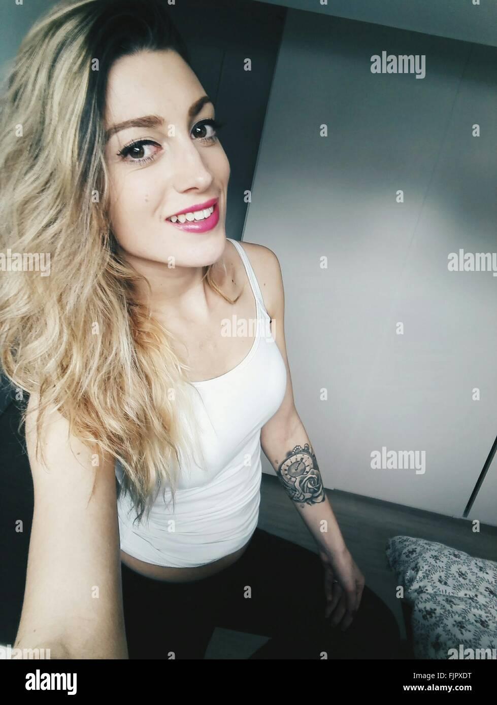 Retrato de hermosa mujer sonriente vistiendo camisetas sin mangas en casa permanente Imagen De Stock