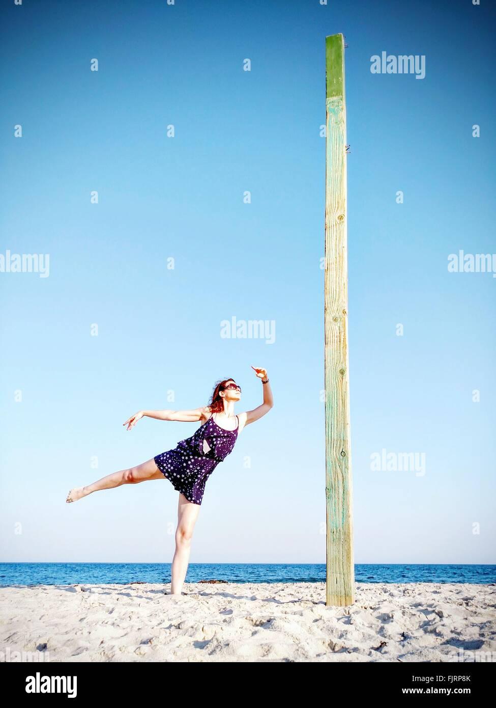 Mujer Bailando en la playa contra el cielo claro Foto de stock