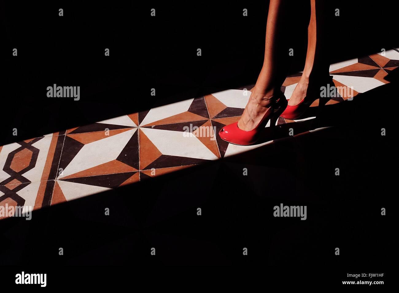 Bajo la sección de Mujer de pie sobre la luz solar por piso de baldosas. Foto de stock