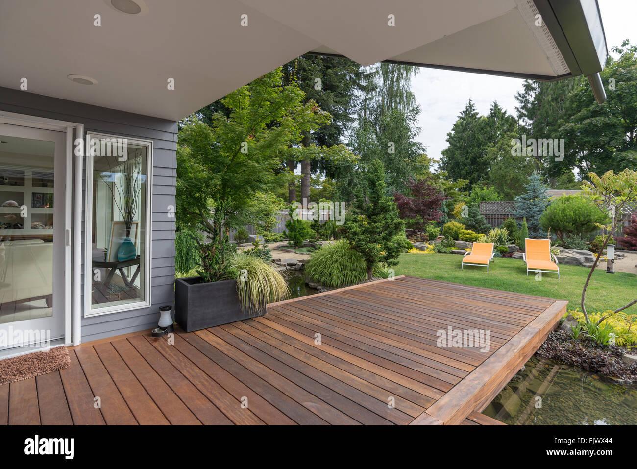 Una perspectiva de una casa del Noroeste del Pacífico contemporáneo con una baraja colmar una laguna que Imagen De Stock