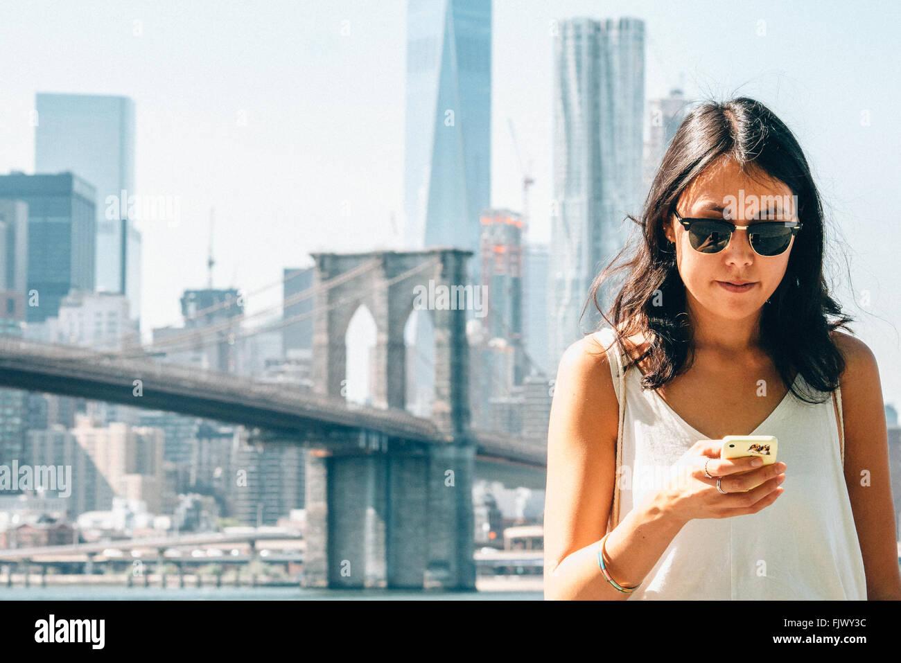Mujer joven con teléfono inteligente contra el Puente de Brooklyn Foto de stock