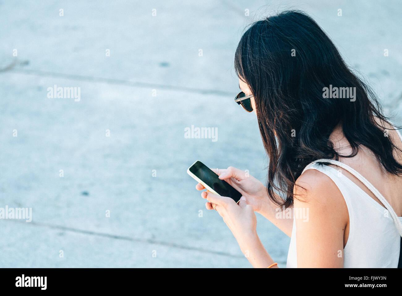 Vista lateral de la mujer utilizando Smart Phone en la calle Imagen De Stock