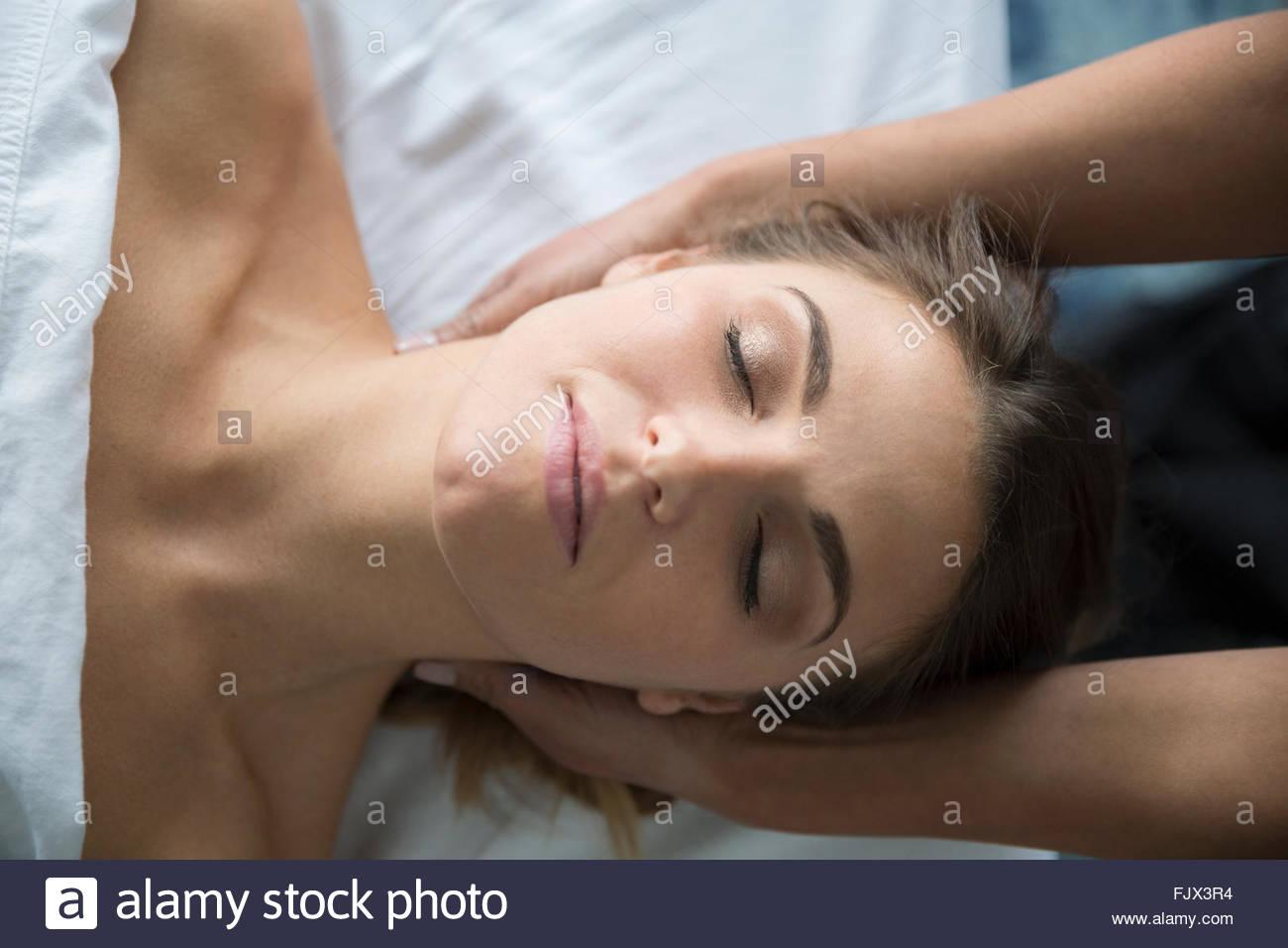 Mujer serena con los ojos cerrados recibiendo masaje de cabeza Foto de stock