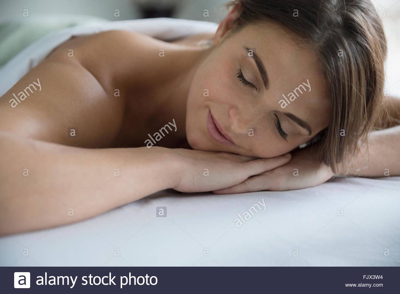 Mujer serena sentar camilla de masaje, con los ojos cerrados Imagen De Stock