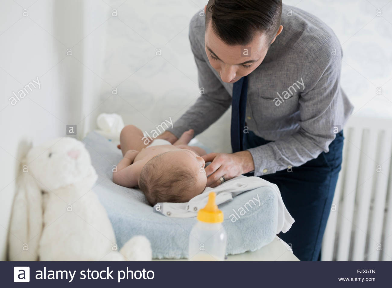 Padre cambiando pañales nursery 2-5 meses. Imagen De Stock