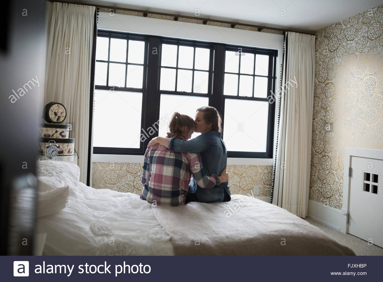Abrazos y besos madre hija adolescente en dormitorio Imagen De Stock