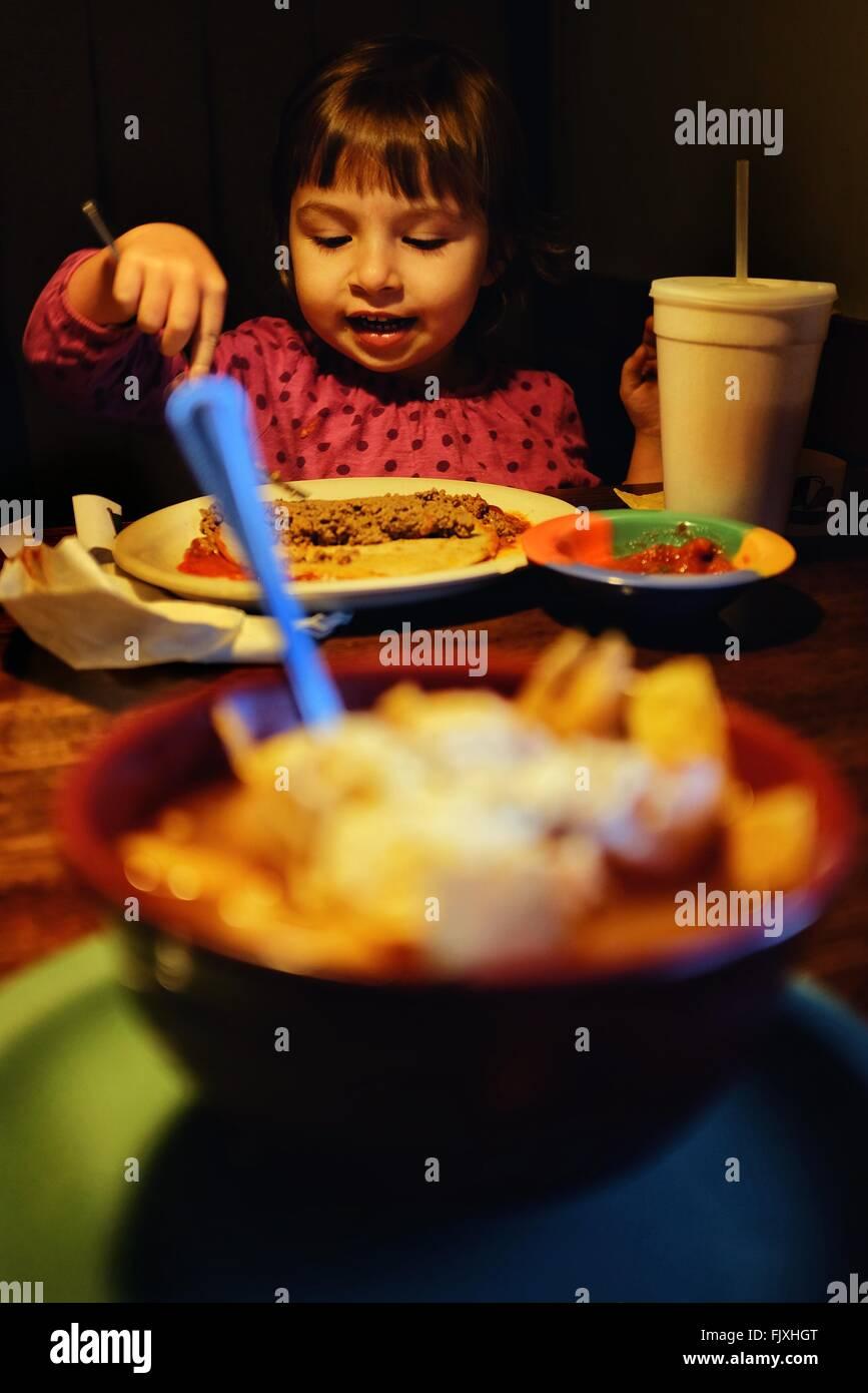 Muchacha comiendo alimentos en los hogares. Foto de stock