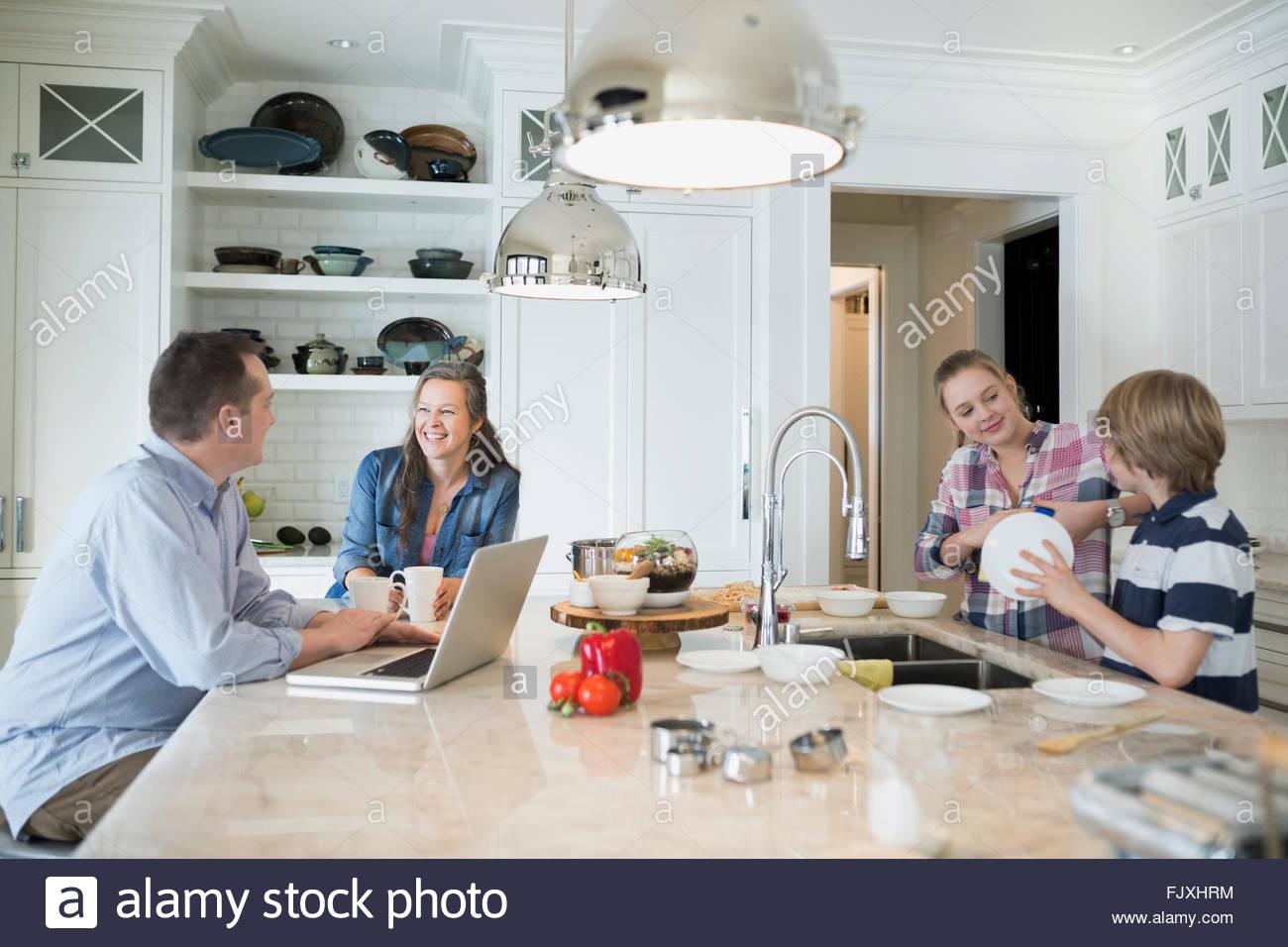 Hermano y hermana, lavar los platos mientras los padres hablan Imagen De Stock