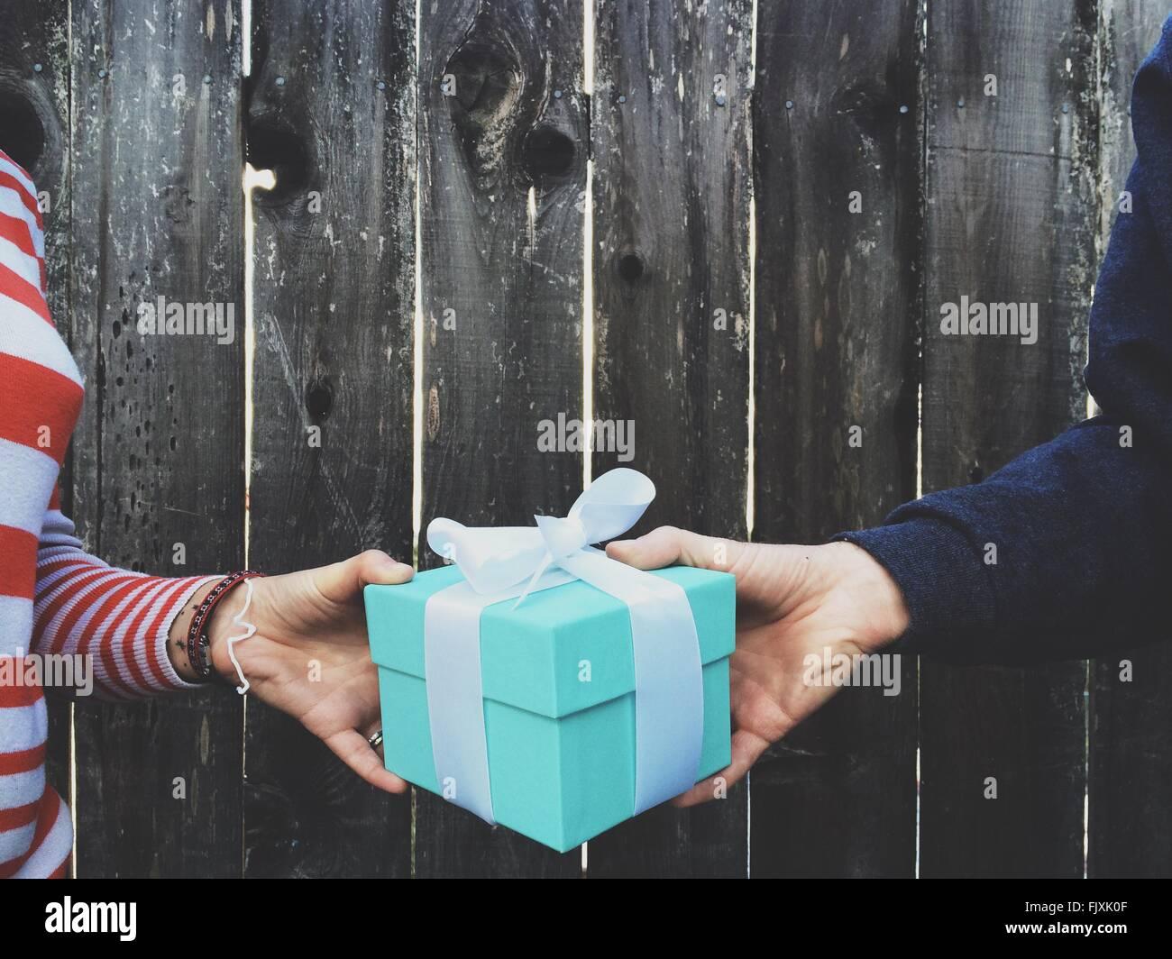 Imagen recortada de manos sosteniendo Caja de regalo contra la valla de madera Imagen De Stock