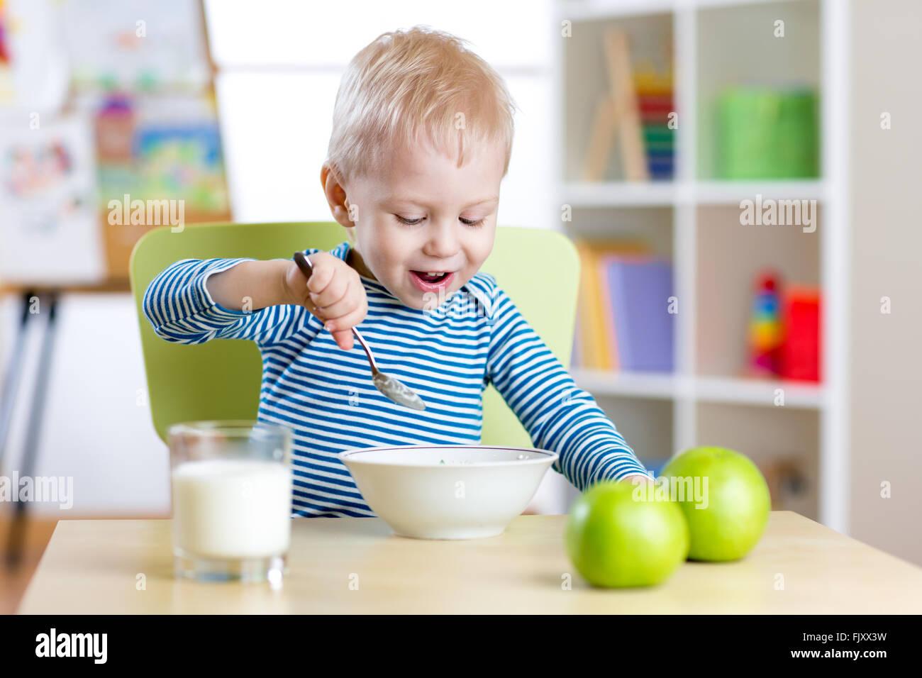Kid comiendo alimentos sanos en el hogar o en el jardín de infantes Imagen De Stock