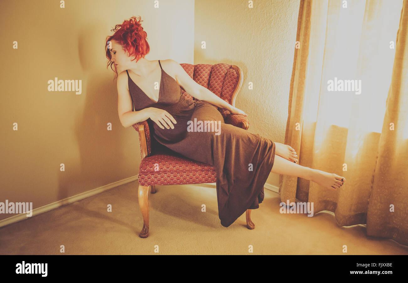 La longitud total del modelo de pasarela sentado en un sillón en casa Imagen De Stock