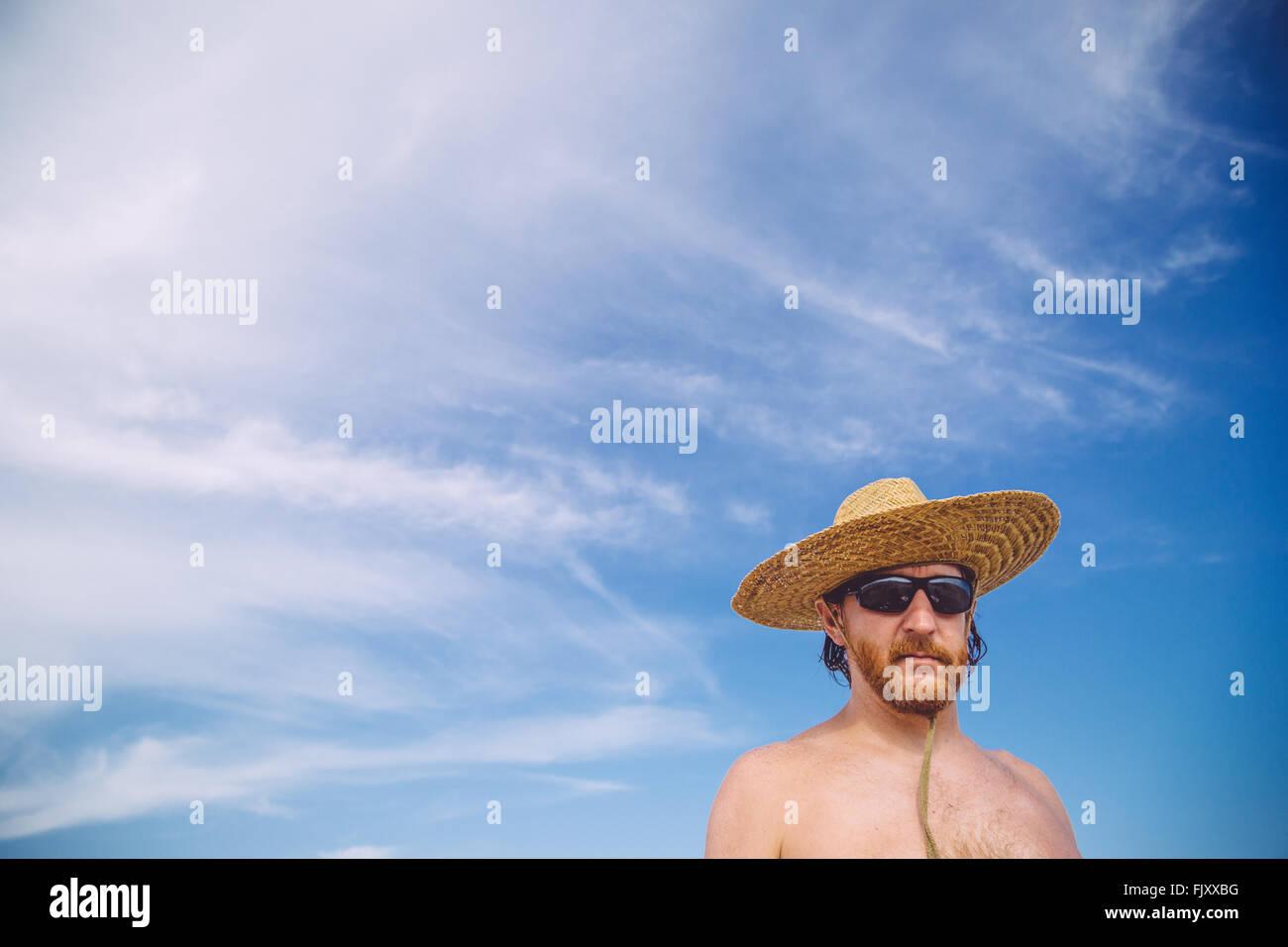 Ángulo de visión baja de descamisados hombre maduro llevar sombrero contra el cielo Imagen De Stock