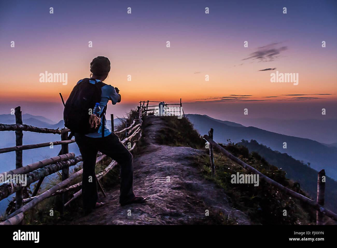 Excursionista de montaña permanente contra el cielo durante la puesta de sol Imagen De Stock