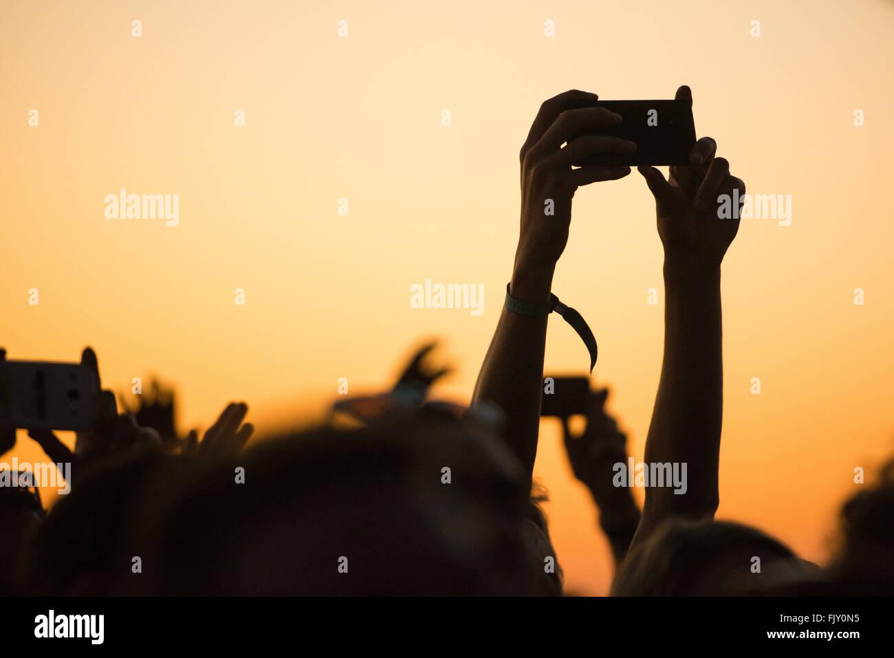 Manos recortadas fotografiar a través de teléfonos inteligentes durante el Festival de Música Imagen De Stock