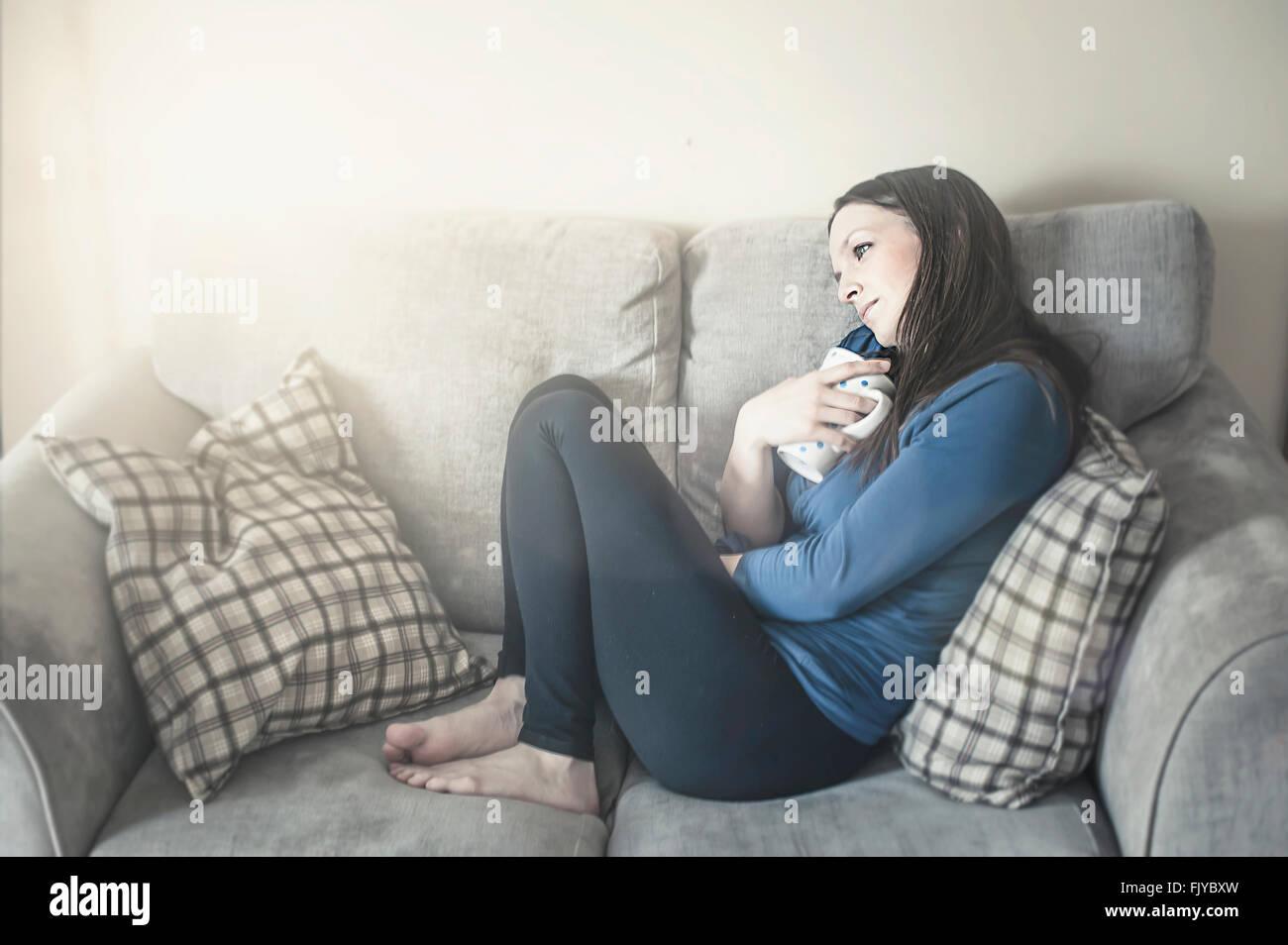 Mujer joven descansando en el sofá-cama Imagen De Stock