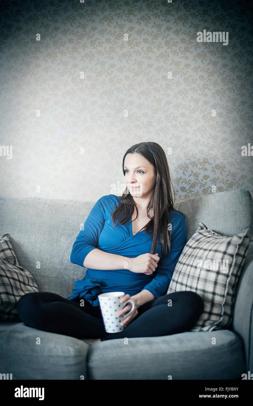 Mujer joven descansando sobre el sofá cama con taza de té Foto de stock