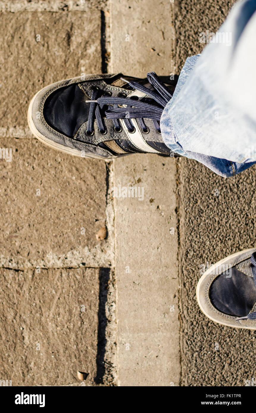Caminé por la línea, un paso adelante ayudan a cruzar la línea y superar un bloque de hormigón. Imagen De Stock